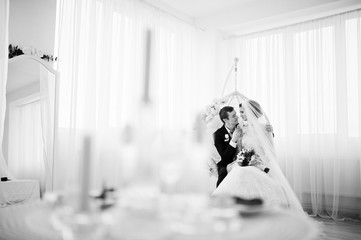 Wedding couple sitting on the floral swing in the studio. Black and white photo.