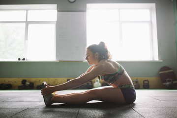 Sporty young girl doing warm-up, stretching muscles on the floor in gymnasium in backlight from window