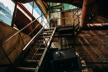Iron rusty staircase in the brick shop of the abandoned factory, inside the interior