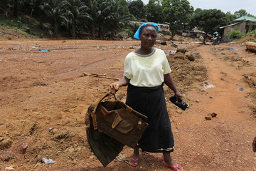 A woman holds a flak jacket of a soldier who she said died rescuing people from the flash flood at Pentagon, Regent town, Sierra Leone