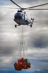 Helicopter carries sling (rope mesh) with empty metal barrels