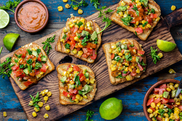 Mexican Latin American style open sandwiches. Vegetarian toasts with maize, avocado, tomatoes on wooden board. Rustic wooden blue background. Top view