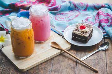 thai tea milkshake and pink milkshake beverage and cake chocolate dessert on wood table