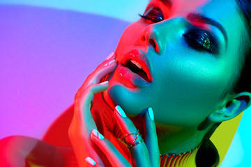 Wall Mural - Fashion model woman in colorful bright lights with trendy make-up and manicure posing in studio