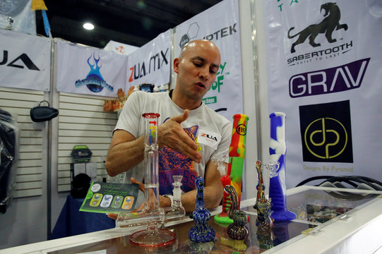 Alexis Zua shows water pipes during the first day of the marijuana fair ExpoWeed in Mexico City