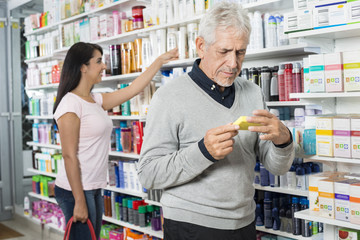 Male And Female Customers Shopping In Pharmacy