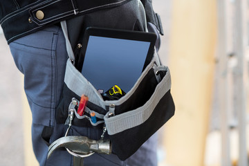 Midsection Of Carpenter With Tablet Computer And Tools In Bag