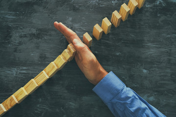 A male hand stopping the domino effect. executive and risk control concept