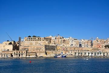 Valletta waterfront buildings including Upper Barrakka Gardens seen from across the Grand Harbour in Vittoriosa, Valletta, Malta.