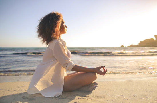 Girl doing yoga at the beach, at sunset time