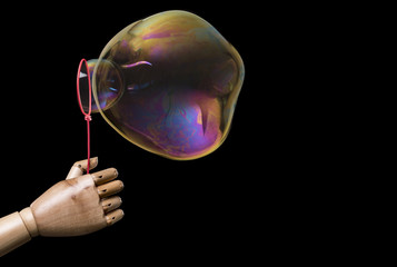 Hand of man creates large soap bubbles. Isolated on dark background. With copy space text. Studio Shot.