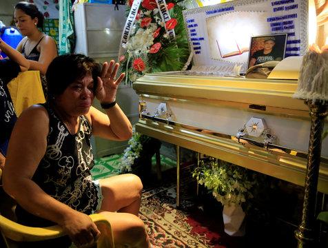 Loreta Amancera, aunt of Wilson Castillo, wipes her tears beside the coffin of her nephew, inside their house in V. Mapa, metro Manila
