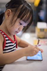 Asian Chinese little girl playing smartphone