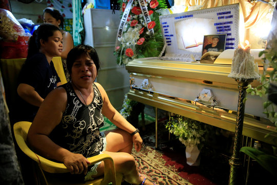 Loreta Amancera, aunt of Wilson Castillo, cries while talking to the media beside the coffin of her nephew, inside their house in V. Mapa, metro Manila