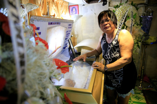 Loreta Amancera, aunt of Wilson Castillo, cries in front of the coffin of her nephew, inside their house in V. Mapa, metro Manila