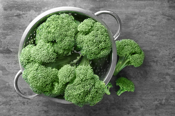 Colander with fresh green broccoli on table