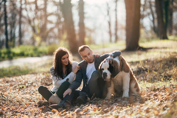 Young couple enjoying nature outdoors together with their adorable Saint Bernard puppy. People and dogs theme.