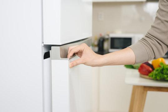 Male hand is opening white refrigerator door