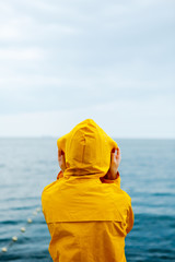 Back view of girl in yellow raincoat standing on stone pier of waterfront with ocean on background.
