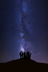 Landscape with milky way, Night sky with stars and silhouette of happy people standing on high moutain