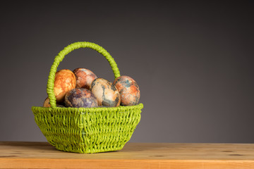 Multicolored hand painted easter eggs in the green basket