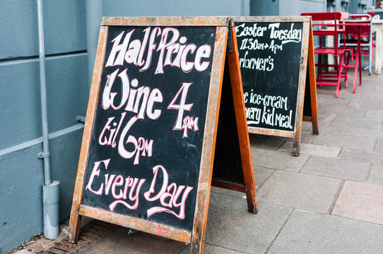 Blackboard A-boards outside a pub cafe advertising half price wine between 4pm and 6pm every day.