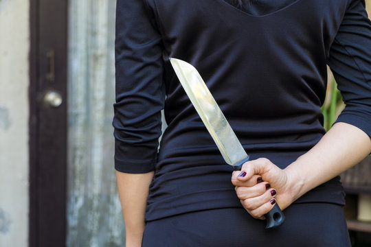 Woman in black holding a knife