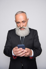 infuriated senior man looking at smartphone