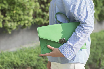 Green leather handbag. Woman in blue blouse holding a small trendy clutch. Smart casual outfit. City life