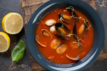 Above view of a dark gray plate with seafood soup, horizontal shot, close-up