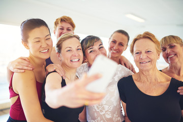 Group of smiling friends taking selfies in a dance studio
