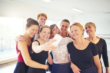 Group of smiling women taking selfies in a dance studio