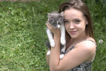 Beautiful smiling girl holding a young cat.