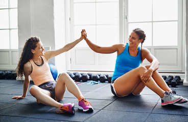 Two smiling female friends high fiving together at the gym