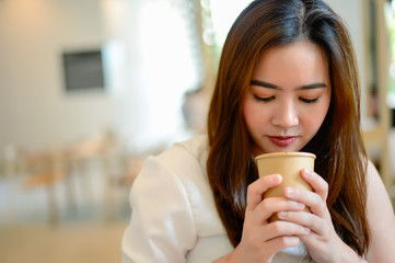 Portrait of beautiful face woman and holding a cup of coffee in her hand in blur background coffee shop, she drink coffee in the morning