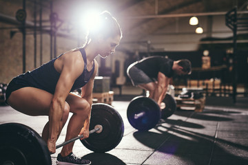 Sportive people holding barbells before doing deadlift