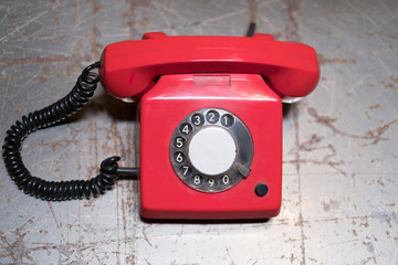 old red phone on table - vintage telephone on desk