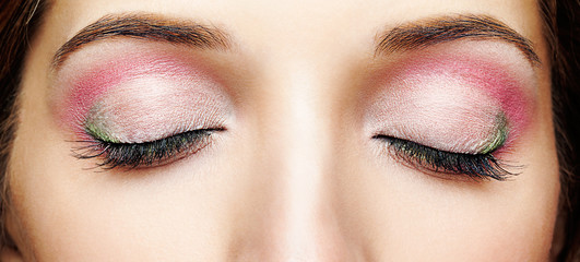 Closeup shot of woman face with closed eyes and pink - green makeup
