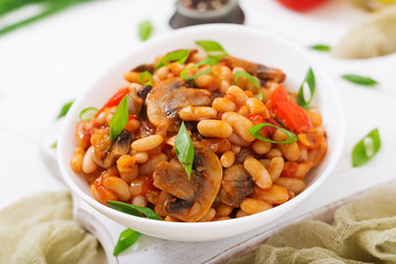 Photo sur Plexiglas Plat cuisine Stewed white beans with mushrooms and tomatoes with spicy sauce in a white bowl.