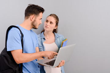 portrait of two student male and female on grey plain background with copyspace