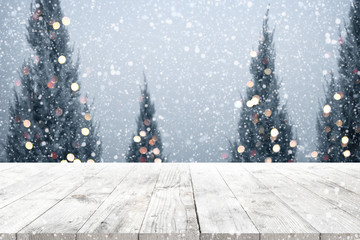 Wall Mural - Christmas and New year background with wooden deck table over christmas tree, snow and blurred light bokeh. Empty display for product montage. Rustic vintage Xmas background.