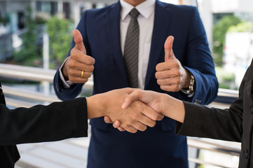 business man show thumb up and two business woman shaking hands for demonstrating their agreement to sign agreement or contract between their firms, companies, enterprises. success concept