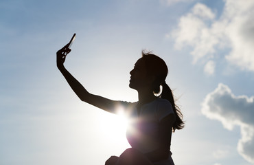 Silhouette of woman taking selfie with mobile phone under sunset