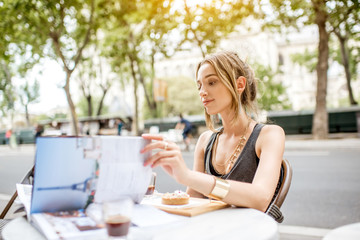Young stylish woman reading journal sitting outdoors at the cafe in Paris