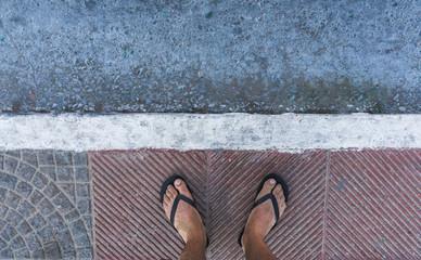 Von oben fotografierte sandige Füße mit  Flip Flops