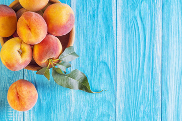 Fresh ripe peaches in a wooden bowl on a blue wooden background.