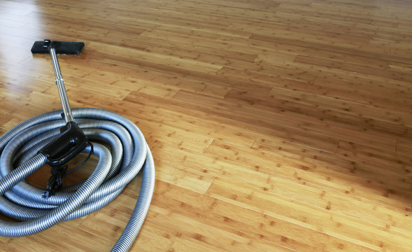 Beautiful bamboo hardwood floor with a central vacuum cleaner. Cleaning contest.