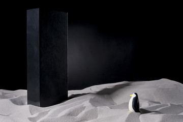 Penguin on the sand meets a monolith. Parody of the film by Stanley Kubrick, 2001 Space Odyssey. With copy space text. Studio Shot. Fotomurales