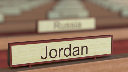 Jordan name sign among different countries plaques at international organization. 3D rendering