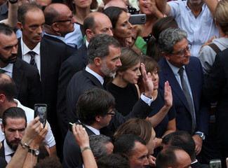 Spain's King Felipe and Queen Letizia wave as they pay respects at an impromptu memorial where a van crashed into pedestrians at Las Ramblas in Barcelona, Spain